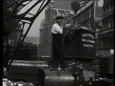 b/w 1927 garbage bin being emptied into truck / garbage man / paris, france - ゴミ収集車点の映像素材/bロール