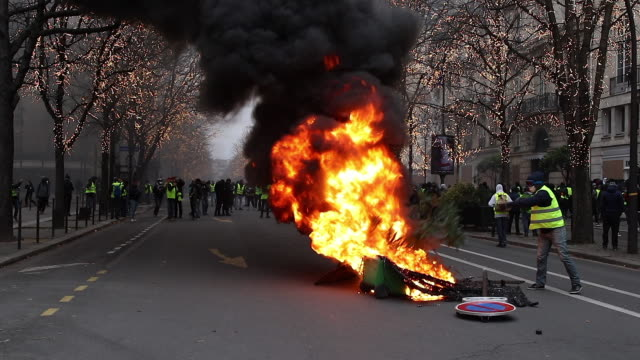 garbage cans burn in the street avenue de Montaigne Paris flame and smoked black people throw things to make a fire
