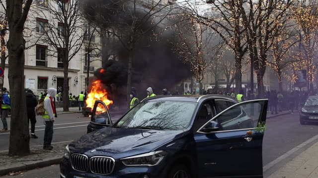 garbage cans burn in the street avenue de Montaigne Paris flame and smoked black a car damaged by projectiles