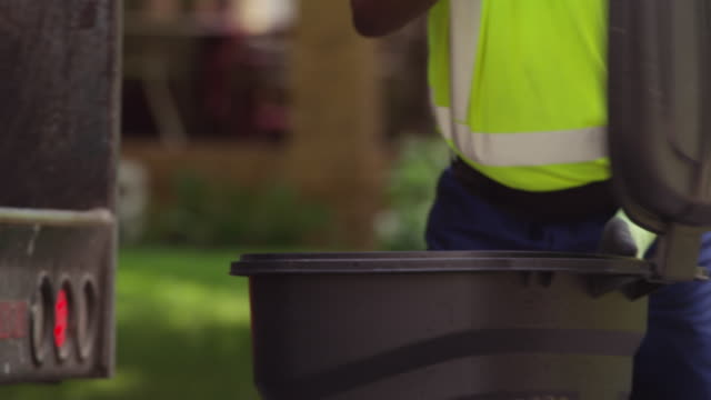 garbage collection worker dumps a trash can of waste into a garbage truck. - one mature man only stock-videos und b-roll-filmmaterial