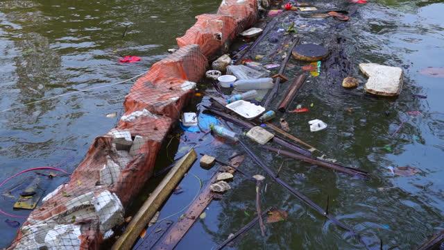 vídeos de stock, filmes e b-roll de garbage floating on river - poluição do plástico