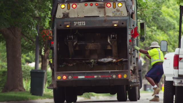 Garbage is compacted in a residential waste collection truck and a worker man climbs aboard.