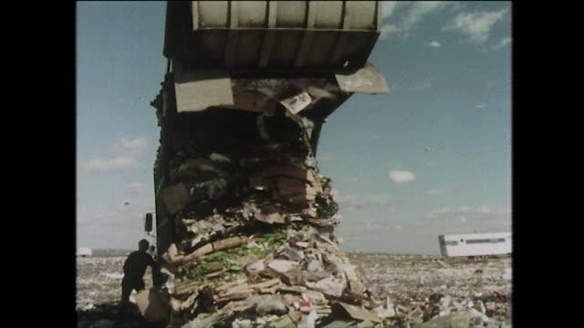 garbage lorry empties its load into landfill; 1975 - ゴミ収集車点の映像素材/bロール