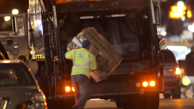 A garbage man puts some corrugated boxed in the back of a garbage truck in NYC at night