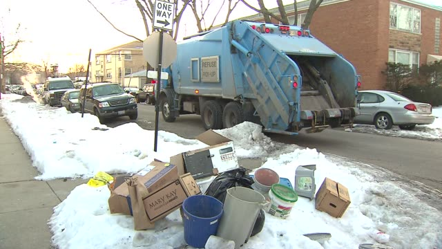 Garbage man throws trash into back of Garbage Truck in Chicago on Feb 12 2015