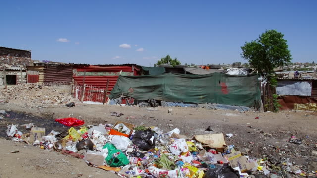 vidéos et rushes de ws garbage on dirt road in town, housing and shacks in background / diepsloot, south africa - cahute