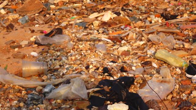 汚れたビーチのゴミ、夕日、石油掘削 - 不完全な美しさ点の映像素材/bロール