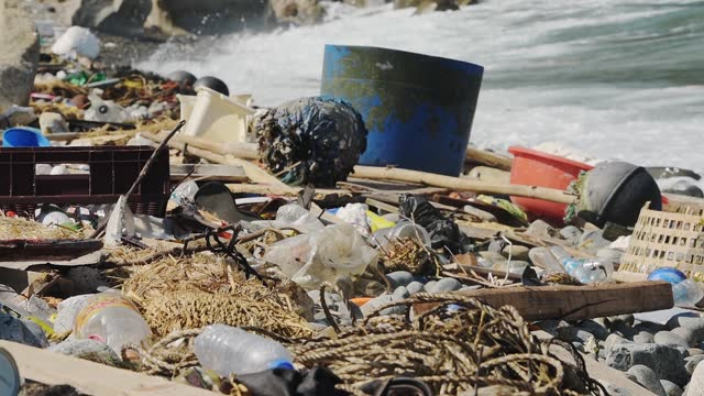 garbage on the rocky shoreline of hongkong beach under the summer weather. -medium shot - plastförorening bildbanksvideor och videomaterial från bakom kulisserna