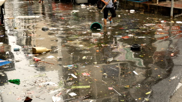 4k video : garbage on water flooding in bangkok,thailand - flood stock videos & royalty-free footage