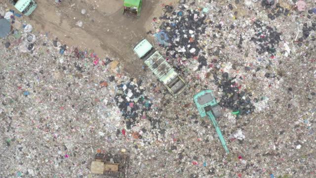 vídeos de stock, filmes e b-roll de lixo ou resíduos montanha ou aterro, caminhões de lixo de vista aérea descarregar lixo para um aterro sanitário. crise de poluição plástica. - símbolo de resíduos biológicos