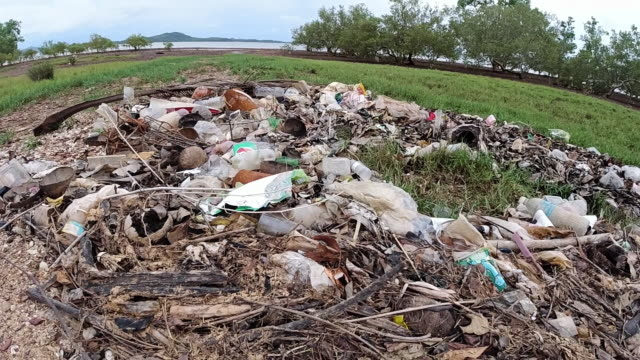 garbage patch of plastic pollution washed up on coastline - littering stock videos & royalty-free footage