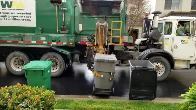 Garbage truck from the waste processing company Waste Management uses an automated arm to pickup a residential trash bin in San Ramon California...