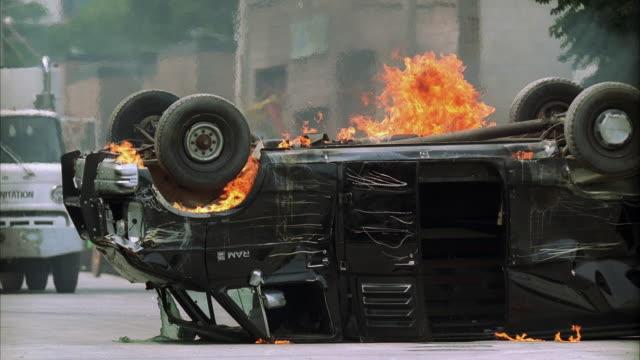 SLO MO MS Garbage truck hitting overturned burning van on city street
