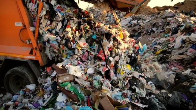 vídeos de stock, filmes e b-roll de caminhão de lixo em um aterro despejando o lixo. veículo que transporta o lixo ao desperdício - depósito de lixo