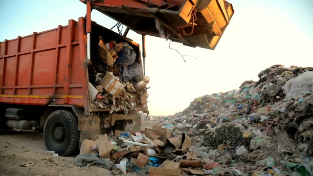 garbage truck on a landfill dumping the garbage.vehicle transporting garbage to waste - garbage truck stock videos & royalty-free footage