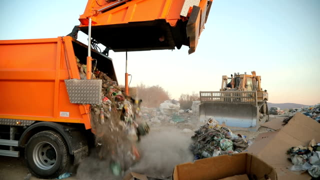 garbage truck on a landfill dumping the garbage.vehicle transporting garbage to waste - waste management stock videos & royalty-free footage