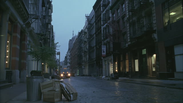 A garbage truck picks up trash along the cobblestone streets of upper class Soho.