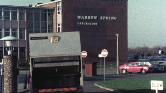 1976 zi garbage truck pulling into laboratory site / hertfordshire, england, united kingdom - ゴミ収集車点の映像素材/bロール
