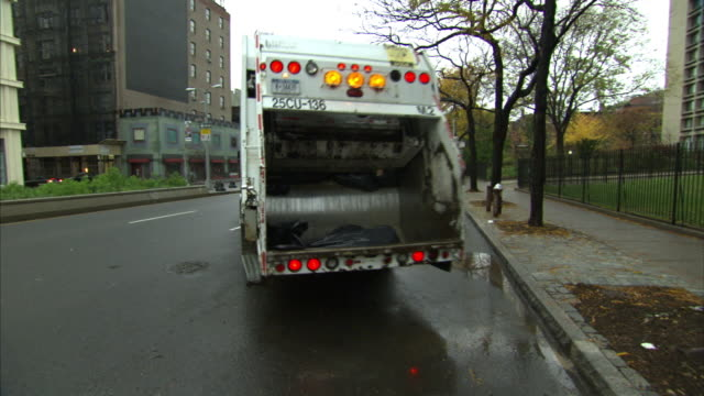 a garbage truck pulls away from a curb. - garbage truck stock videos and b-roll footage