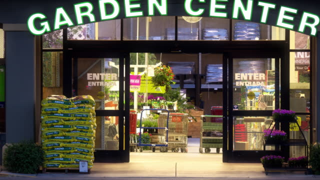 T/L  garden center department at big box hardware store stocking gardening supplies  as shoppers enter and exit store / La Quinta, California, USA