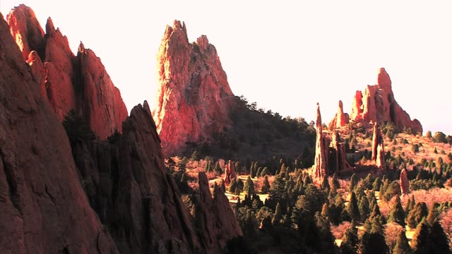 Garden of the Gods park including views of the famous Pikes Peak and people hiking among red rock formations and wildlife that call the urban park...