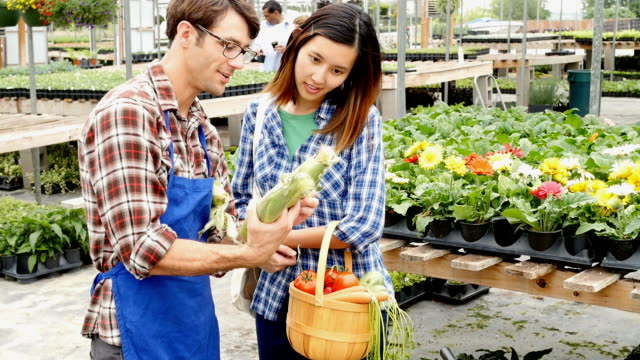Garden store employee helps Vietnamese woman choose vegetables