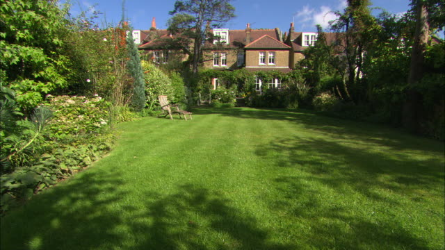 ws of garden with house in bg, deckchair in fg - front or back yard stock videos & royalty-free footage