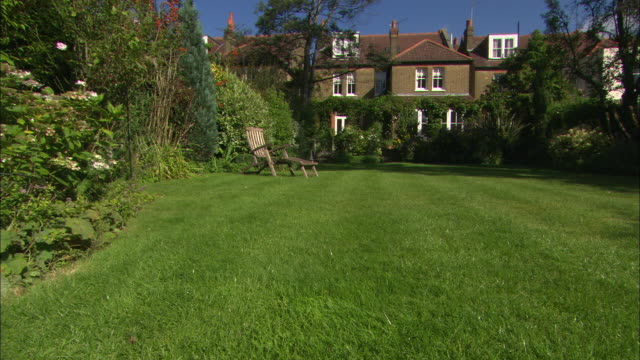 WS of garden with house in BG, deckchair in FG