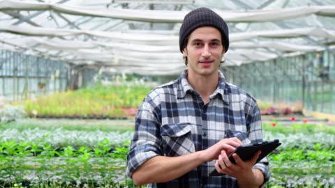 gardener in garden center with a digital tablet - organic farm stock videos & royalty-free footage