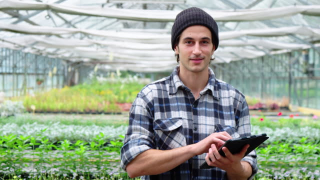 gärtner im gartencenter mit digitalem tablet - portrait stock-videos und b-roll-filmmaterial