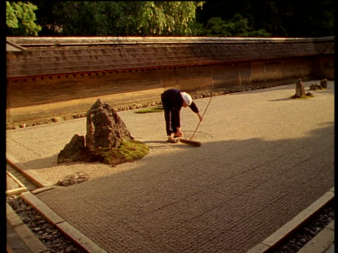 a gardener rakes patterns in gravel in the ryoan-ji zen garden. - oriental garden stock videos and b-roll footage