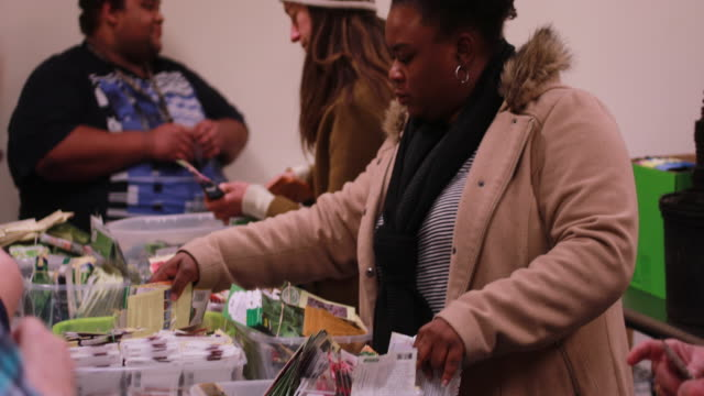 gardeners browse free packages of gardening seeds during the seed and supply swap at mother hubbard's cupboard monday february 18 2019 in bloomington... - plant attribute stock videos and b-roll footage