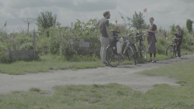 gardeners work in allotments in berlin germany on friday july 28 cyclists pass the allotments - gemeinschaftsgarten stock-videos und b-roll-filmmaterial