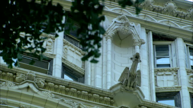 a gargoyle on an apartment building overlooks the trees below. - gothic stock videos & royalty-free footage