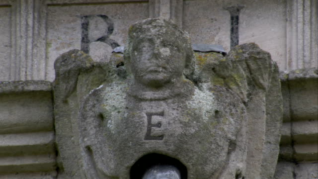 vídeos y material grabado en eventos de stock de a gargoyle with a letter e inscribed in its chest perches on the corner of rushton triangular lodge in northamptonshire, england. available in hd. - northamptonshire