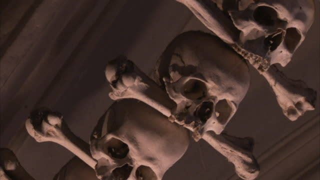 vídeos de stock, filmes e b-roll de a garland of human skulls and bones hanging from the ossary ceiling. available in hd. - osso