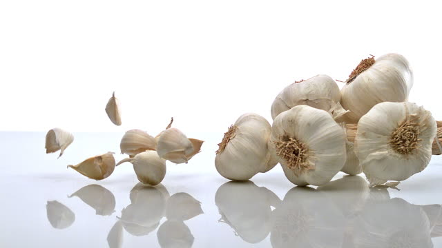 garlic, allium savitum, falling against white background, slow motion - garlic stock videos & royalty-free footage