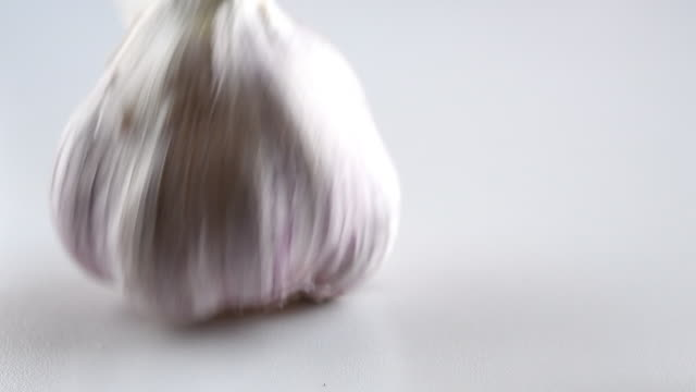 garlic heads or bulbs moving in slow motion over a white surface - garlic stock videos & royalty-free footage