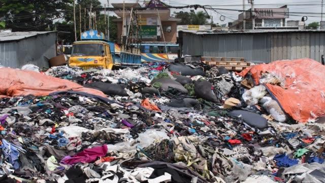 vídeos de stock e filmes b-roll de garment factory waste at a dumping site in dhaka - indústria têxtil