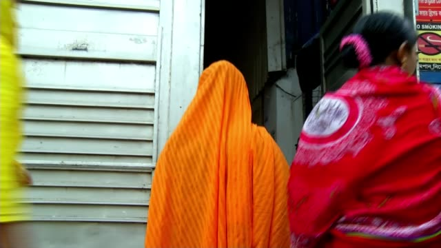 garment industry staffed by workers displaced by climate change vox pops [interpreter translating] various shots garment workers along into factory... - kleidungsstück stock-videos und b-roll-filmmaterial
