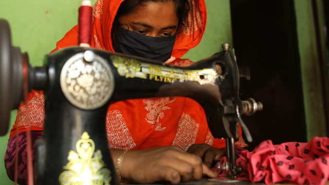 vídeos y material grabado en eventos de stock de garment worker sewing clothes inside a rented room in dhaka, bangladesh on april 22, 2021. she loses her job during coronavirus pandemic and now... - modo de vida no saludable