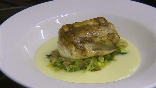 garnishing a monkfish meat dish - ひれ点の映像素材/bロール