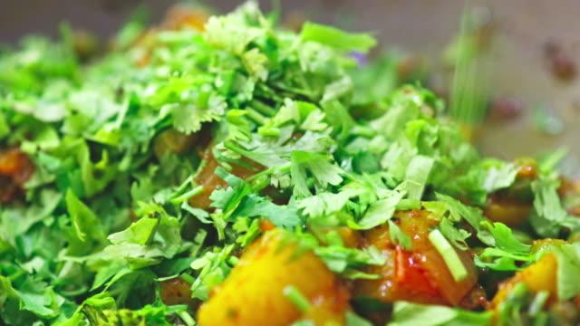 garnishing fresh cilantro over a potato curry - coriander stock videos & royalty-free footage