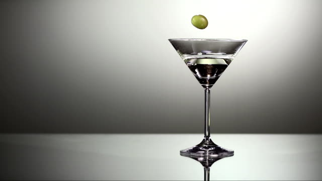 stockvideo's en b-roll-footage met garnishing martini with olive (super slow motion) - martiniglas