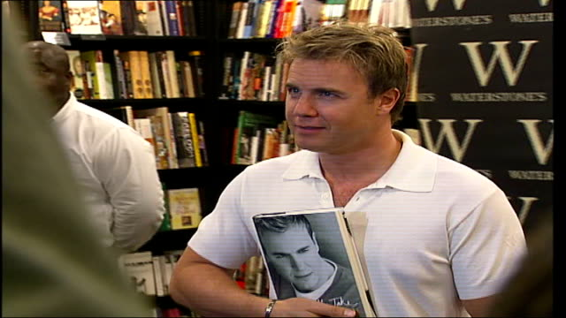 vidéos et rushes de gary barlow book signing and interview gary barlow posing for photocall as holding autobiography zoom in / high angle shot of take that fans waiting... - autobiographie