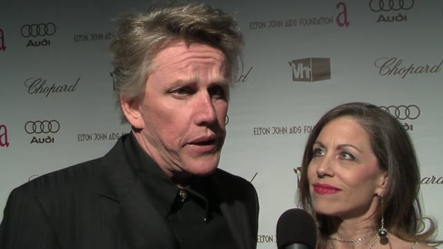 gary busey, with guest vicki roberts, on being at elton john's party for the first time, and on elton john's foundation fighting aids at the 14th... - ゲーリー ビジー点の映像素材/bロール