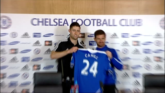 gary cahill photocall on signing for chelsea england surrey cobham throughout** gary cahill photocall holding chelsea football shirt with chelsea... - コブハム点の映像素材/bロール