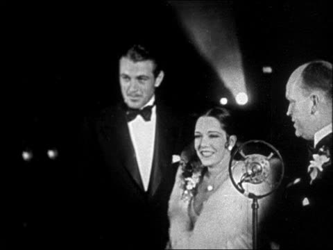 "vídeos y material grabado en eventos de stock de gary cooper + lupe velez posing for photos at ""interference"" premiere / newsreel - pareja de mediana edad"