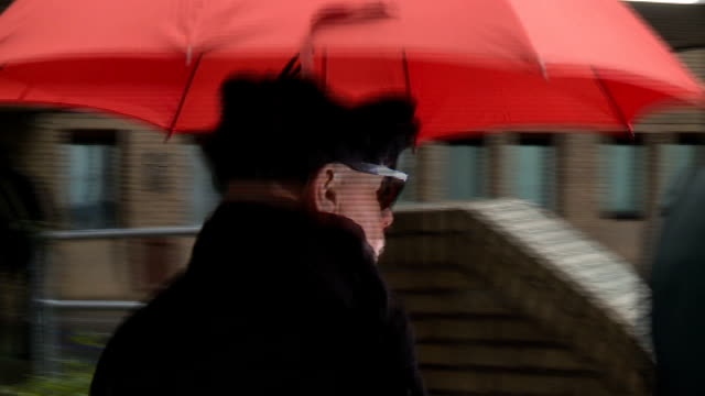 gary glitter arrival at court; england: london: southwark: ext / raining gary glitter , carrying red umbrella, along road to court - gary glitter stock videos & royalty-free footage