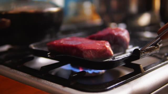 vídeos de stock, filmes e b-roll de gas burner and raw steak on a pan. - skillet cooking pan